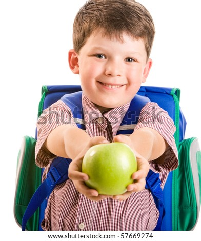 Portrait of cute smiling schoolboy giving a green apple - stock photo