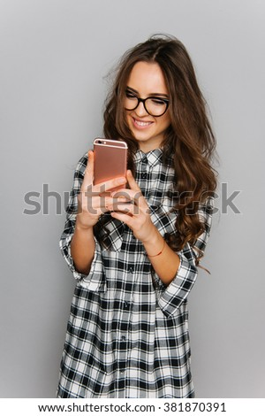 Portrait of cute teen girl texting emotional isolated on gray studio background posing to the camera - stock photo
