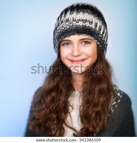 Portrait of cute teen girl wearing stylish knitted hat and sweater isolated on blue background, winter fashion for teenagers - stock photo