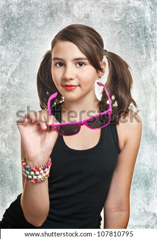 Portrait of cute teen girl with pony tails looking at camera over textured  background - stock photo