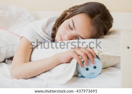 Portrait of cute teenage girl holding alarm clock under pillow - stock photo