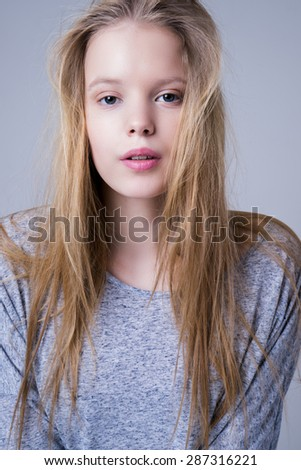 Portrait of cute teenage girl or student female on gray - stock photo