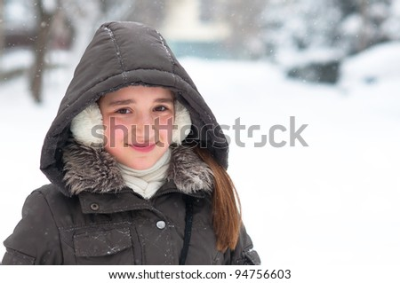 Portrait of cute teenage girl posing outside on beautiful winter day.