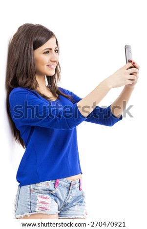 Portrait of cute teenage girl taking self portrait with her smart phone over white background - stock photo