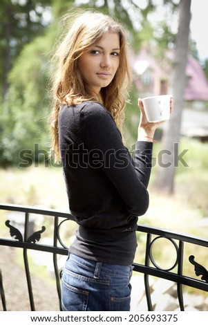 Portrait of cute teenage girl with cup of coffee on the terrace - stock photo