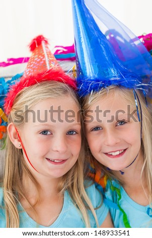 Portrait of cute twins during their birthday party - stock photo