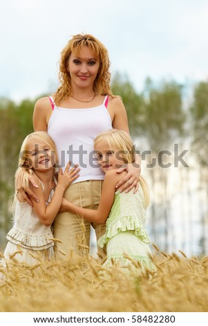 Portrait of cute twins embracing their mother with smiles in wheat field - stock photo
