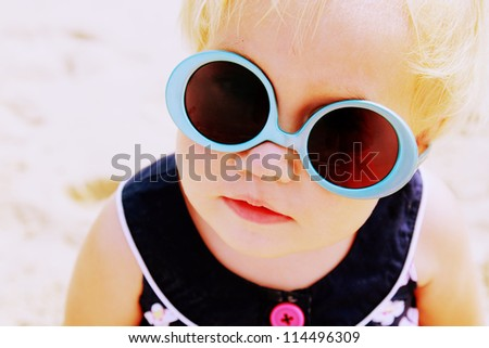 Portrait of cute 1,5 years old baby with fashin vintage sunglasses. sunglasses worn on the contrary - stock photo