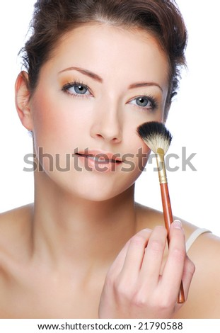 Portrait of cute young adult woman cleaning face after applying make-up - stock photo