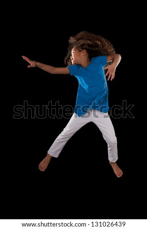 Portrait of cute Young African American girl jumping, over black background - stock photo