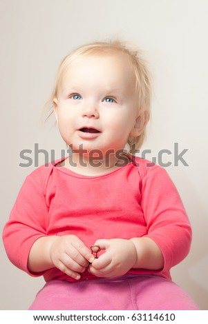 Portrait of cute young baby sit on chair and  grimacing - stock photo
