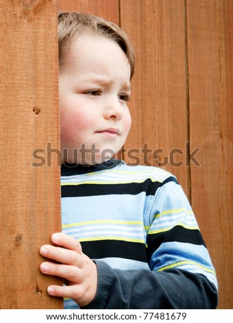 Portrait of cute young boy by fence.