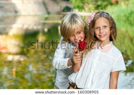 Portrait of cute young boy giving red rose to girl at lakeside. - stock photo
