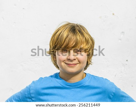portrait of cute young boy in sunlight with white wall - stock photo