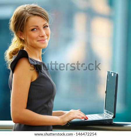 Portrait of cute young business woman near office building with laptop