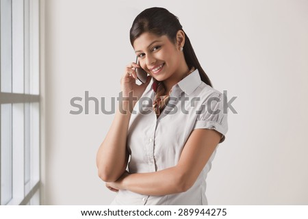 Portrait of cute young business woman on phone call at officePortrait of cute young business woman on phone call at office - stock photo