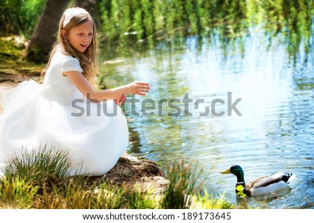 Portrait of cute young girl feeding a duck at riverside. - stock photo