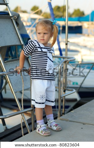 Portrait of cute young girl in yacht harbor in sailor suit - stock photo