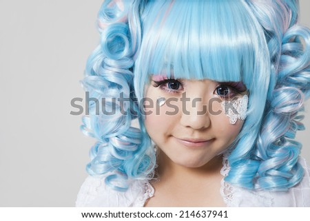 Portrait of cute young woman in doll costume over gray background