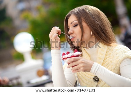 Portrait of cute young woman sitting in a cafe outdoor tasting a dessert