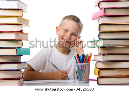 Portrait of cute youngster sitting among stacks of literature and smiling at camera while drawing