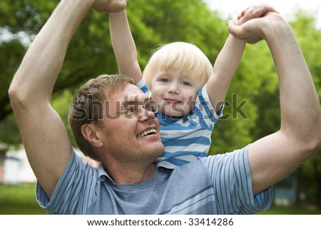 Portrait of daddy playing his son outdoor - stock photo