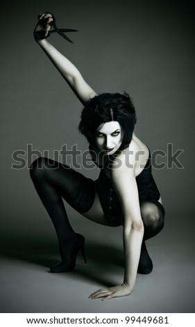 Portrait of dangerous and sexy goth girl with scissors in hand - stock photo