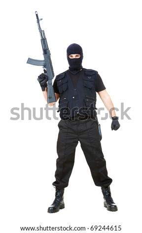 Portrait of dangerous bandit in black wearing balaclava and holding gun in hand - stock photo