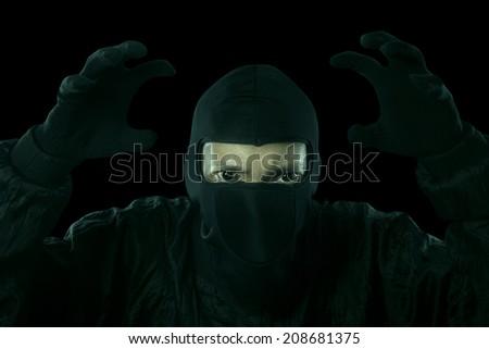 Portrait of dangerous bandit in dark background - stock photo