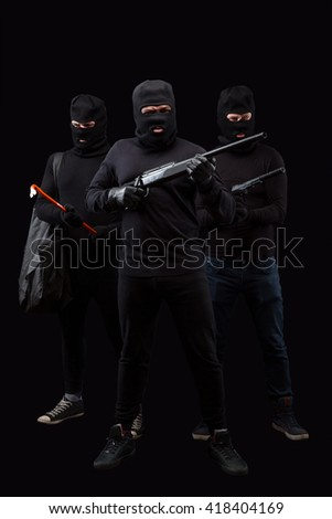 Portrait of dangerous robbers with rifles and crowbars over black background. Men in black balaclavas posing in full length in studio. Isolated on black. - stock photo