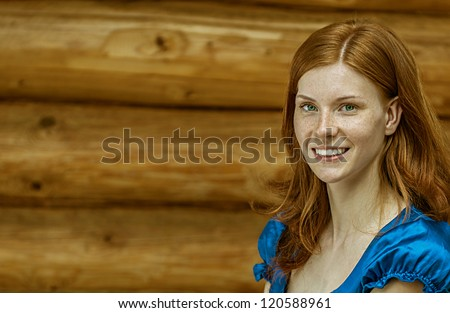 Portrait of dark-haired beautiful young woman in blue blouse, against background of log hut - stock photo