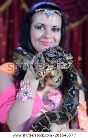 Portrait of Dark Haired Exotic Snake Charmer Female Dancer with Large Snake Around Neck Smiling at Camera - stock photo