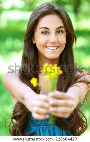 Portrait of dark-haired smiling nice young woman with yellow flowers, against background of summer green park.