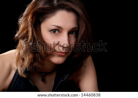 Portrait of dark-haired woman isolated at the black background