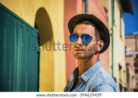 Portrait of dark haired young man in blue mirrored sunglasses and black hat. Cityscape on background, with colorful houses in Italy  - stock photo