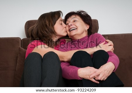 Portrait of daughter kissing happy senior mother sitting on sofa at home - stock photo