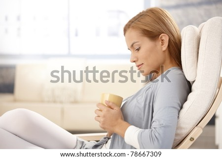 Portrait of daydreaming pretty woman sitting with tea cup handheld, looking down, smiling.? - stock photo