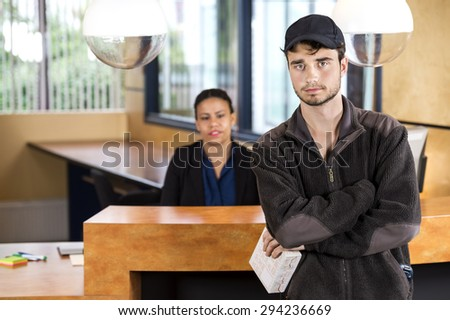 Portrait of delivery man holding package while standing at reception counter in office - stock photo