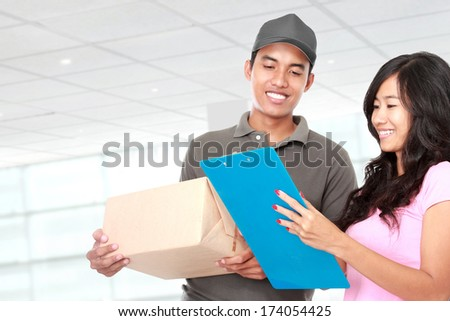 portrait of Delivery man sending the package to young woman - stock photo
