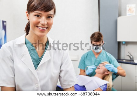 Portrait of dental assistant smiling with dentistry work in the background - stock photo