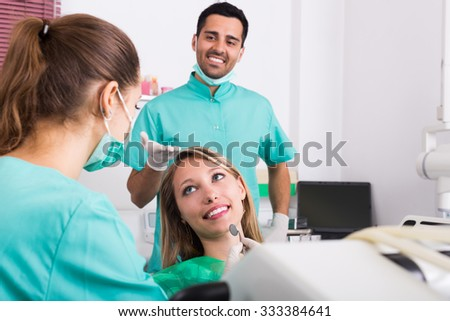 Portrait of dentist and positive patient at dental clinic - stock photo