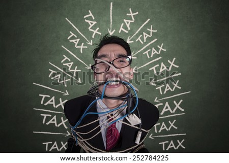 Portrait of depressed manager having tax trouble bound by rope and cable - stock photo