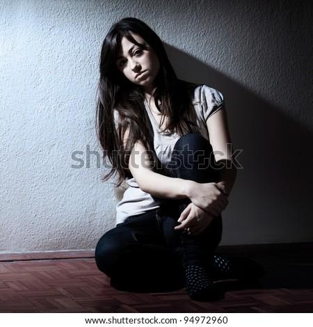 Portrait of depressed teenage girl sitting on floor. - stock photo