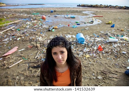Portrait of depressed woman standing in front of rubbish and recycle dirty beach - stock photo