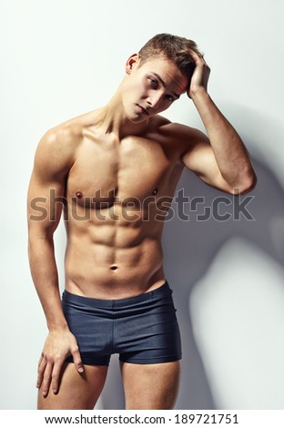 Portrait of depressive young muscular man in underwear with headache against white wall
