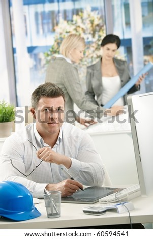 Portrait of designer at work, using drawing pad, with coworkers working in background.?