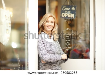 Portrait of designer woman standing in front of small vintage store. Small business. - stock photo