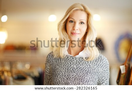 Portrait of designer woman standing in her clothing shop. Small business - stock photo