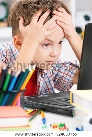 Portrait of despairing adolescent boy working on computer at the table - stock photo