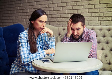 portrait of despondent couple looking at laptop